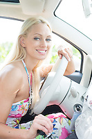 Portrait of happy woman sitting in car