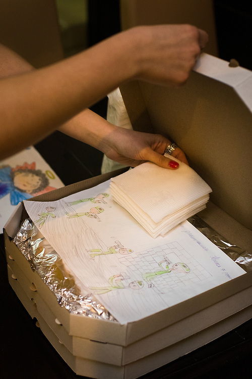 Waitress Veronica Ryzhenkowa places napkins and a drawing made by local children in a box with a donated pizza that will be given to deploying soldiers at Veterano Pizza on January 24, 2016 in Kiev, Ukraine. (Pete Kiehart for The New York Times)