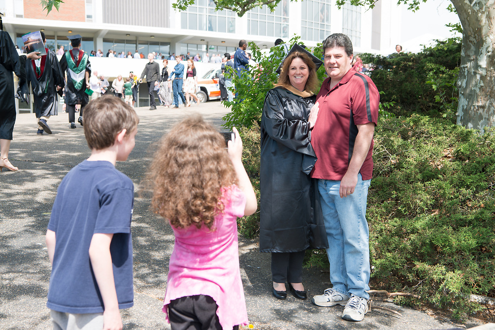 Marie Sandy commemorates receiveing her MBA with her family following graduate commencement ceremonies. Photo By Ben Siegel