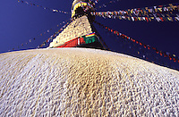 Brightly coloured prayer flags and textures surface of the Bodnath Stupa in the Kathmandu Valley.
