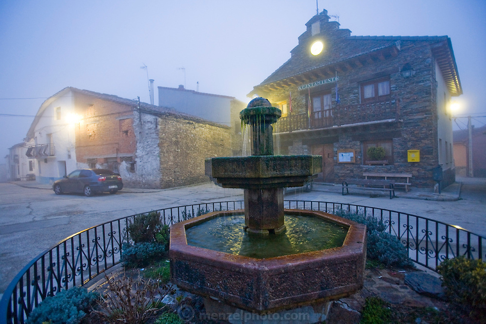 Fog envelopes old bulildings in the village of Zarzuela de Jadraque, Spain on a cold morning at dawn.