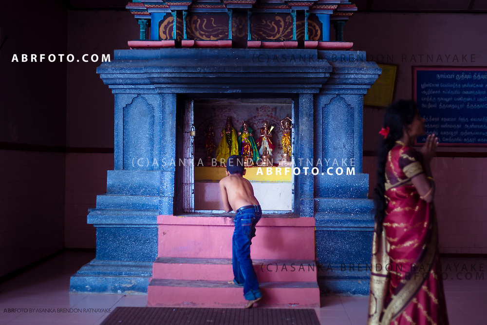 A young boys reaches into to touch the statue inside the shrine as his mother prays inside the Nagabooshani Amman Kovil or temple on Nagadeepa island.