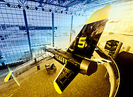 """Grumman F11(F-11) Tiger jet seen from above, suspended from Cradle of Aviation museum ceiling. """"U.S. NAVY"""" printed in yellow on blue plane. Ultra wide angle view of 3 floor atrium lobby. Long Island air and space Museum, Museum Row, Garden City, Long Island, New York, USA. Atmospheric rendering with blue, yellow, gold, black."""