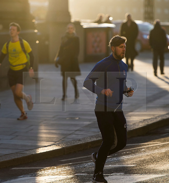 © Licensed to London News Pictures. 28/01/2016. London, UK. A jogger crosses a road in warm sunshine in Westminster on a clear day at sunrise in London on a cold winter morning. Photo credit: Ben Cawthra/LNP