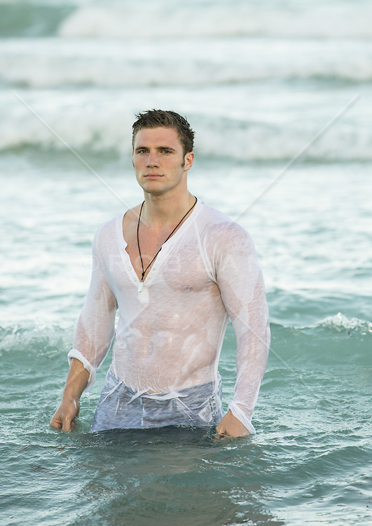 sexy man in wet clothes standing in the ocean