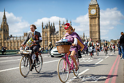 © Licensed to London News Pictures. 18/04/2015. LONDON, UK. Participants of The Tweed Run crossing Westminster Bridge in London on Saturday, 18 April 2015. Ten-mile bicycle ride aimed at revisiting the fashions and pastimes of the polite aspects of 1920's to 1950's England. Photo credit : Tolga Akmen/LNP