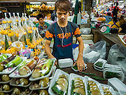 "21 DECEMBER 2015 - BANGKOK, THAILAND:  A man bundles packages sold for Buddhist merit making in Pak Khlong Talat, also called the Flower Market. The market has been a Bangkok landmark for more than 50 years and is the largest wholesale flower market in Bangkok. A recent renovation resulted in many stalls being closed to make room for chain restaurants to attract tourists. Now Bangkok city officials are threatening to evict sidewalk vendors who line the outside of the market. Evicting the sidewalk vendors is a part of a citywide effort to ""clean up"" Bangkok.      PHOTO BY JACK KURTZ"