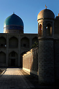 Low angle view of Memorial complex of Chor-Bakr, 16th century, Bukhara, Uzbekistan, pictured on July 10, 2010 in the afternoon light. This view shows the side portal decorated with two stories of loggias and the blue dome of the mosque in the background.  Bukhara, a city on the Silk Route is about 2500 years old. Its long history is displayed both through the impressive monuments and the overall town planning and architecture.