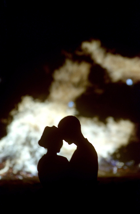 A couples shows affection at a high school bon fire.