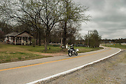 Bill Dragoo rides past an old farmhouse with chicken coops situated along Oklahoma State Highway 20 north of Spavinaw.