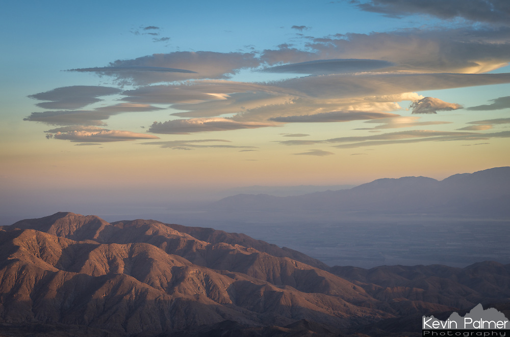 These little lenticular clouds repeatedly formed over the same area as seen from Keys View. Lenticular clouds form when strong winds encounter a mountain range. The air is forced upward where it condenses into a cloud. These strange disc-shaped clouds form often in the California desert.<br />