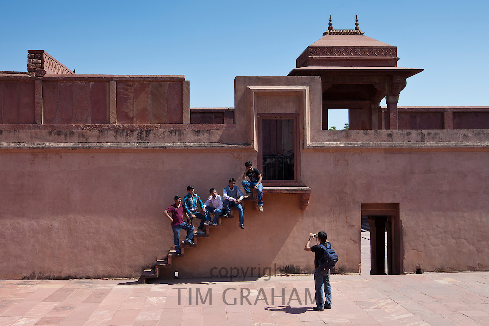 Young Indian men being photographed while visiting Fatehpur Sikri historic palace and city of Mughals, at Agra, Northern India