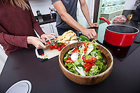 Midsection of couple cooking together at kitchen counter