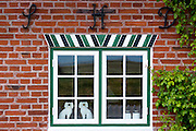 Traditional Staffordshire dog figurines in window of quaint cottage house on Fano Island, South Jutland, Denmark