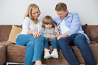 Parents sitting with sad son on sofa at home