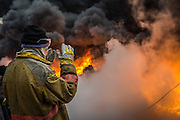 A firefighter shields his face from the scorching heat emanating from the flames of an oil well fire in the Qayyarah oil field on December 12, 2016.