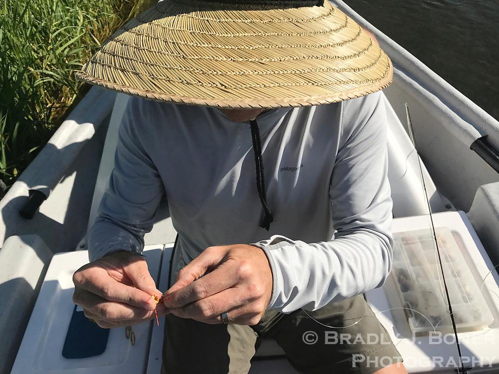 Dan Bierman ties a yellow stonefly while fishing on the Teton River in Teton Valley, Idaho.