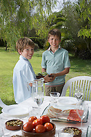 Portrait of two boys (6-11) by table in garden