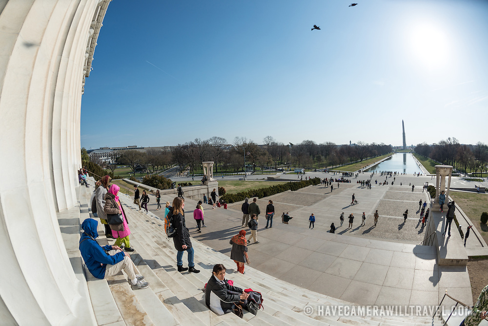 Tourists sit on the steps of the Lincoln Memorial in the sun in Washington DC. In the distance at right is the newly renovated Reflecting Pool and the Washington Monument partly covered in scaffolding.