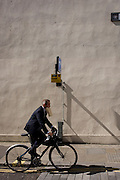 A businessmen cycles past carrying a package in his mouth in the City of London.