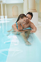 Young couple talking at edge of swimming pool