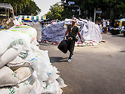 """30 DECEMBER 2013 - BANGKOK, THAILAND:   An anti-government protestor walks past a bunker guarding the intersection of Phitsanulok and Ratchadamnoen Roads. Violence around the anti-government protest sites has escalated in recent days and several protestors have been hurt by small explosive devices thrown at their guard posts. As a result, protestors are fortifying their positions with sandbags and bunkers. Suthep Thaugsuban, the leader of the anti-government protests in Bangkok, has called for a new series of massive protests after the 1st of the year and said it the shutdown, or what he described was the seizure of the capital, would be the day when """"People's Revolution"""" would """"begin to end and uproot the Thaksin regime.""""        PHOTO BY JACK KURTZ"""