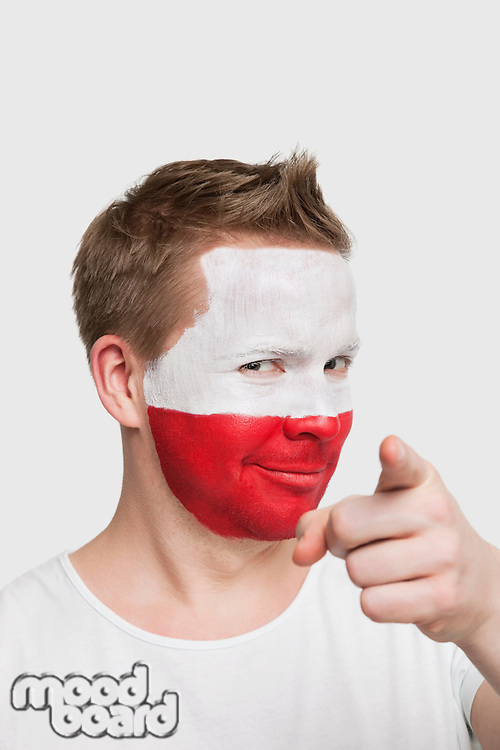 Portrait of young man with Polish flag painted on face pointing finger against white background