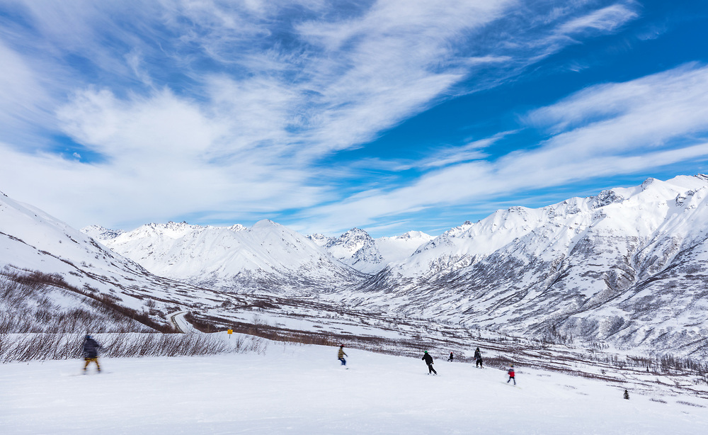 Snowboarders descending into the valley at Hatcher Pass State Recreation Area in Southcentral Alaska. Winter. Afternoon.