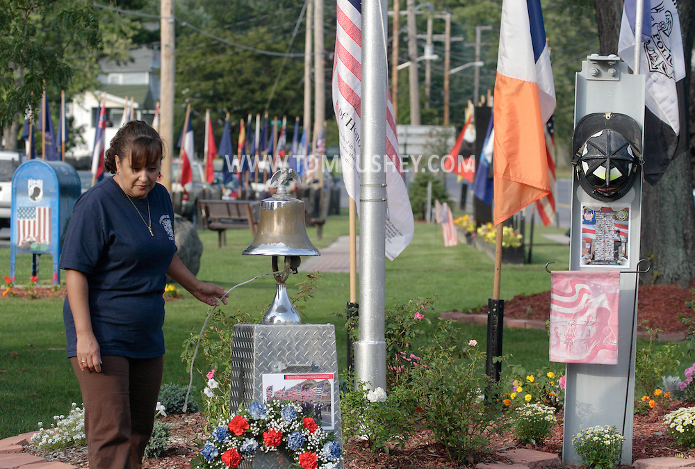 Town of Wallkill, NY - A woman rings a bell after reading the name of a local person killed in the World Trade Center terrorist attack during a 9-11 memorial ceremony on Sept. 11, 2008.