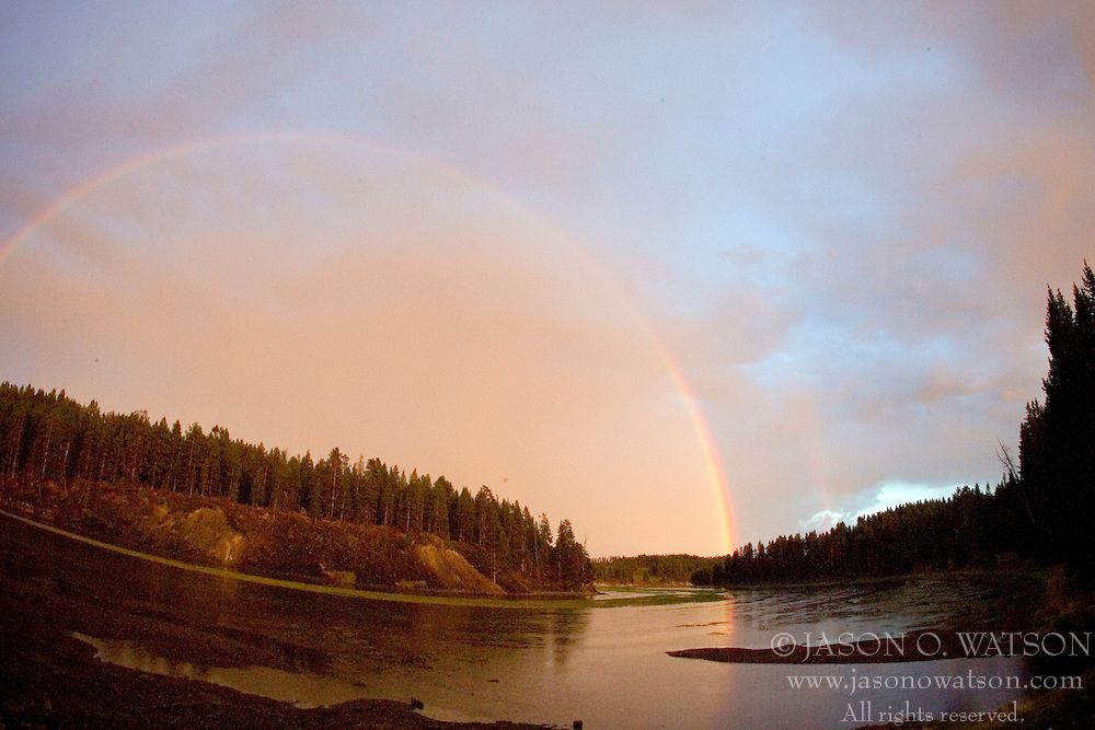 A twilight rainbow forms over the Yellowstone River - after sunset - in Yellowstone National Park, Wyoming.