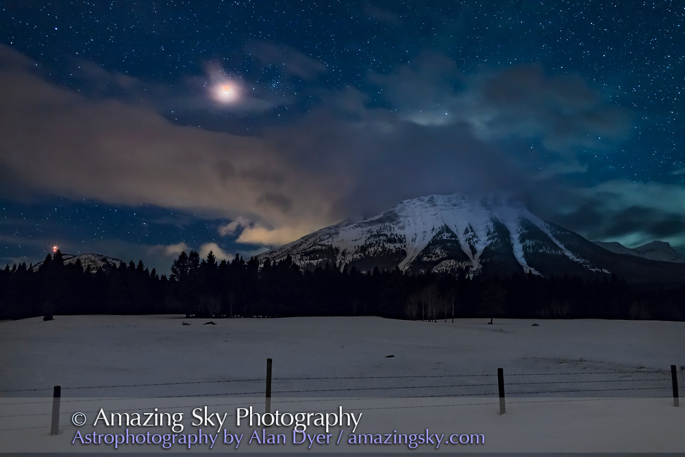 The total eclipse of the Moon on January 31, 2018 from the Crowsnest Pass area of the Alberta Rocky Mountains near the Continental Divide. The eclipsed Moon is in clouds wafting off the peaks. <br /> <br /> This was about 6:05 am MST, about 10 minutes after the start of totality when the bottom edge of the Moon was still quite bright. <br /> <br /> The star cluster right of the Moon is M44, the Beehive. <br /> <br /> This was from near Coleman, Alberta. <br /> <br /> The Moon and sky is a 7-image blend of short to long exposures (blended with luminosity masks) to better retain the Moon and its red colour during totality. The ground is a 4-image mean combined stack to smooth noise. <br /> <br /> All were with the 35mm Canon lens at f/2.8 and Canon 6D MkII at ISO 800, and untracked.