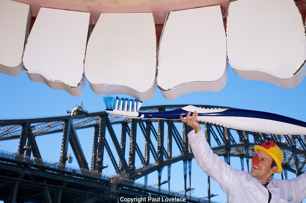 Luna Park's Teeth get a giant brush for national smile day, Sydney-Australia 1 Apr 2010.Paul Binney cleans the teeth. . An instant sale option is available where a price can be agreed on image useage size. Please contact me if this option is preferred.