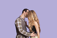 Side view of young couple kissing over purple background
