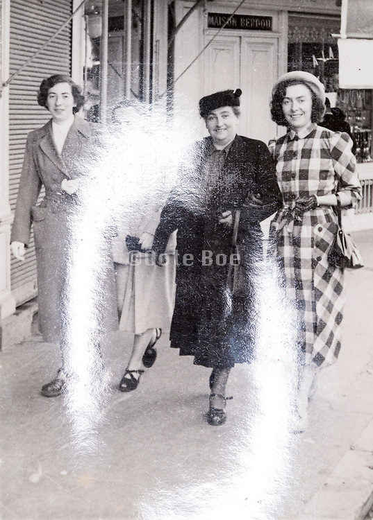 happy smiling female only group together walking in the street France ca 1950s with photo surface light reflection