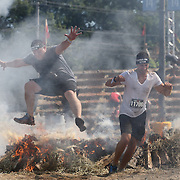 Taylor Lee, (left) and Alexander Tudor in action at the fire jump obstacle during the Reebok Spartan Race. Mohegan Sun, Uncasville, Connecticut, USA. 28th June 2014. Photo Tim Clayton