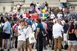 © Licensed to London News Pictures. 14/07/2018. London, UK. Tourists take a selfie as supporters of EDL founder Tommy Robinson ( real name Stephen Yaxley-Lennon ) and US President Donald Trump congregate in Trafalgar Square during a day of demonstrations and rallies in support and opposed to US President Donald Trump and jailed EDL founder Tommy Robinson . Trump is currently in Scotland and Robinson is in HMP Hull . Photo credit: Joel Goodman/LNP