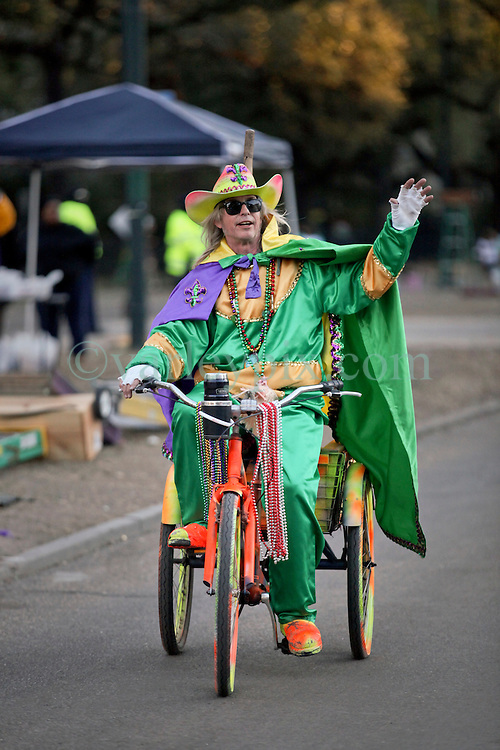 09 February 2016. New Orleans, Louisiana.<br /> Mardi Gras Day. A man dressed in costume rides the parade route along St Charles Avenue in the early morning hours. The main Mardi Gras Parades of Zulu and Rex pass by later in the day.<br /> Photo©; Charlie Varley/varleypix.com