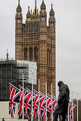 © Licensed to London News Pictures. 30/01/2020. London, UK. Flags fly behind a statue of former Prime Minister Winston Churchill on Parliament Square on the last day before Brexit which will happen tomorrow at 11pm on 31st January 2020. A Brexit party on Parliament Square has also been arranged for tomorrow night. Photo credit: Alex Lentati/LNP