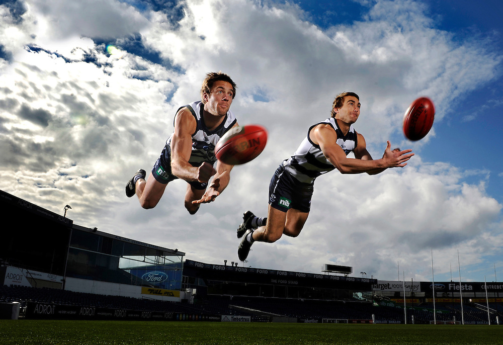 Geelong Cats footballers Joel Corey, left, and Corey Enright show all their usual flair and athleticism when leaping simultaneously in the air while executing a diving handpass for the camera.<br />