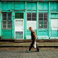 A man wearing cap walking past a colourful old building in Chinatown.