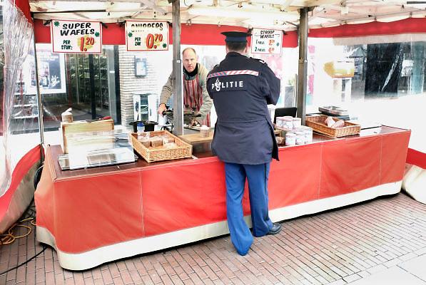 Nederland, Nijmegen, 4-3-2012Een politieagent praat met een marktkoopman die stroopwafels verkoopt.Tijdens de markt houdt de politie extra toezicht.Foto: Flip Franssen/Hollandse Hoogte