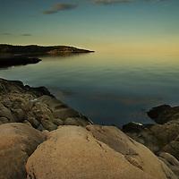 A calm sea with rocky shore