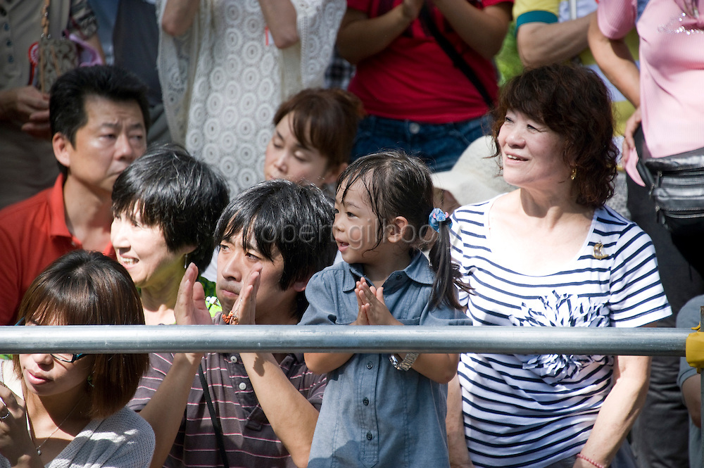 Visitors enjoy the yabusame horseback archery ritual during the annual Reitaisai Grand Festival at Tsurugaoka Hachimangu Shrine in Kamakura, Japan on  14 Sept. 2012.  Sept 14 marks the first day of the 3-day Reitaisai festival, which starts early in the morning when shrine priests and officials perform a purification ritual in the ocean during a rite known as hamaorisai and limaxes with a display of yabusame horseback archery. Photographer: Robert Gilhooly