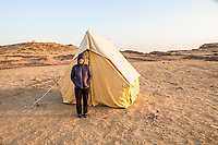 A woman traveler standing outside a tent in the Thar Desert of Rajasthan, India while on an overnight camel trek.