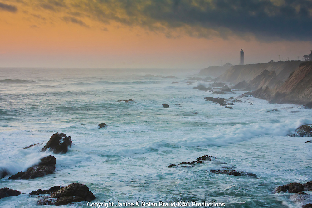 Sunset at Point Arena Lighthouse, which is cloaked in mist created by crashing waves, salt spray, and stormy weather. Point Arena Lighthouse is situated at the end of Point Arena peninsula on the rocky pacific coast of northern California. The original lighthouse was completed in 1870, but was later rebuilt with reinforced concrete after an earthquake in 1906 destroyed the original. Originally fitted with a first order Fresnel Lens (which can be seen in the museum), It was automated on 1977.