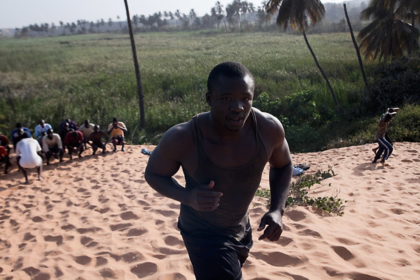 """La Dune...Papa Sow, Lamb's wrestler, age 28, 96kg, 1.77 mt, member of Ecurie Fass from Parcelles, one of the most famous team of traditional wrestling in Senegal, is making an extremely hard daily training, to build up strength. Dakar, Senegal, on tuesday, April 07 2009.....""""Lamb, the wolof word for fight, is a very popular type of African wrestling in Senegal. This """"lutte traditionelle"""" has been transformed into a national cult, drawing massive following next only to football. Senegalese wrestlers are among the best-known national sports figures. The senegalese fight form allows blows with the hands (frappe), the only of the West African to do so. The lutteurs wrestle in a sandy arena and attempt to win by making their opponent's knees, shoulder, or back touch the sand. Matches are festive and lively occasions, with music, dancing, and praise singing for the athletes; the actual wrestling bouts, however, are often over within a few seconds. Presently, wrestling is arranged by business-promoters who offer prizes for the winners..The sport has produced its own legends, names such as Yékini, Tyson and Bombardier (stage names) are celebrities in Senegal. In particular Mohammed Ndao, aka Tyson,  the 34-year-old leader of the Boul Falé generation of Pikine, a Dakar suburb, did not only revolutionise the sport, by carving his own group identity, and upsetting the old guard, but he is also credited with insisting on commensurate remuneration for the wrestlers. A """"combat"""" could start from 10 million CFA francs (about 20,000 US dollars) to 65 million CFA francs. (about 130,000 dollars). The phenomenal success is such that stakeholders are already talking about building a separate stadium for the sport in the country."""""""