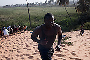 "La Dune...Papa Sow, Lamb's wrestler, age 28, 96kg, 1.77 mt, member of Ecurie Fass from Parcelles, one of the most famous team of traditional wrestling in Senegal, is making an extremely hard daily training, to build up strength. Dakar, Senegal, on tuesday, April 07 2009.....""Lamb, the wolof word for fight, is a very popular type of African wrestling in Senegal. This ""lutte traditionelle"" has been transformed into a national cult, drawing massive following next only to football. Senegalese wrestlers are among the best-known national sports figures. The senegalese fight form allows blows with the hands (frappe), the only of the West African to do so. The lutteurs wrestle in a sandy arena and attempt to win by making their opponent's knees, shoulder, or back touch the sand. Matches are festive and lively occasions, with music, dancing, and praise singing for the athletes; the actual wrestling bouts, however, are often over within a few seconds. Presently, wrestling is arranged by business-promoters who offer prizes for the winners..The sport has produced its own legends, names such as Yékini, Tyson and Bombardier (stage names) are celebrities in Senegal. In particular Mohammed Ndao, aka Tyson,  the 34-year-old leader of the Boul Falé generation of Pikine, a Dakar suburb, did not only revolutionise the sport, by carving his own group identity, and upsetting the old guard, but he is also credited with insisting on commensurate remuneration for the wrestlers. A ""combat"" could start from 10 million CFA francs (about 20,000 US dollars) to 65 million CFA francs. (about 130,000 dollars). The phenomenal success is such that stakeholders are already talking about building a separate stadium for the sport in the country."""