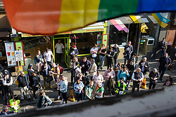 London, UK. 30th April 2019. Viewed from an upper window of the Admiral Duncan pub, members of the LGBTQ community begin to gather outside in Old Compton Street to join survivors of the Admiral Duncan bombing and families and friends of the victims to mark 20 years since the attack. Three people were killed and 79 injured when a bomb packed with up to 1,500 four-inch nails was detonated by a neo-Nazi at the Admiral Duncan on 30th April 1999.