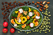 Healthy vegan salad with radish, nuts, yellow pepper on dark slate with copy space