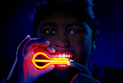 Young girl with glowing jaw harp.Black light